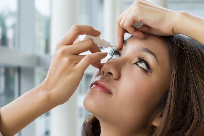 Woman using eye drops to treat dry eye